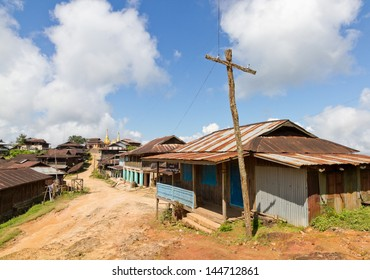 Mud bare earth village lane with wooden huts with corrugated sheet iron metal roofs and wooden makeshift electricity pole. A golden temple stupa at the end.