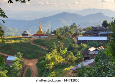 Mud bare earth village with wooden huts with corrugated sheet iron metal roofs and golden temple stupa at the end.