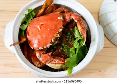 mud crab with glass noodles cooked and served in a clay pot