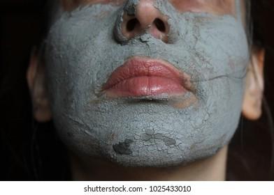 Mud facial mask of woman - close up