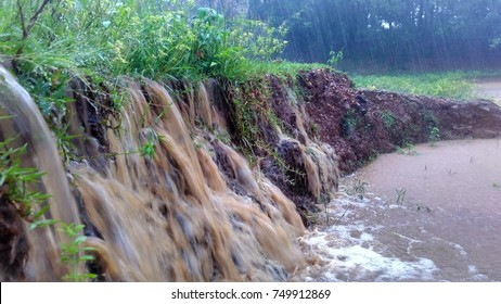 Mud and flowing water reach a pond / swamp during heavy rain looks like water fall causing soil erosion with wave and splash