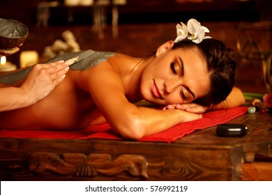 Mud mask of woman in spa salon. Back massage with clay full body . Girl on Luxary interior with candles in oriental therapy room. Female lying on wooden spa bed.