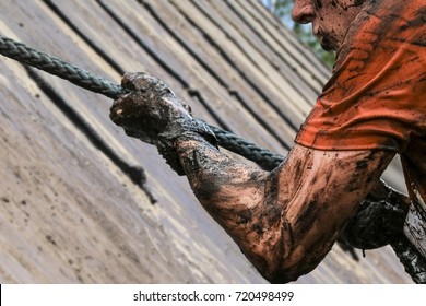 Mud race runners, defeating obstacles by using ropes