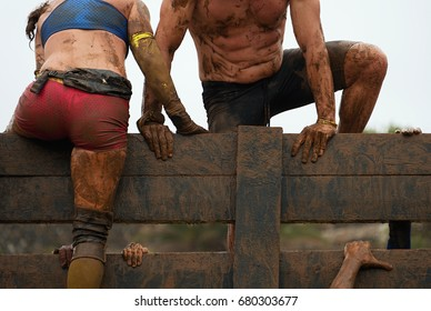 Mud race runners participants overcome obstacles