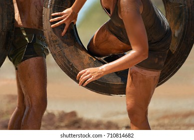 Mud race runners i will overcome the obstacle from hanging tires