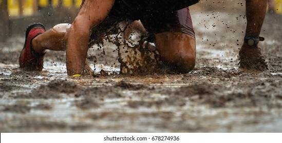 Schlammrennläufer.Crawling, der unter Stacheldraht-Hindernissen während des extremen Hindernisrennen unter einem extremen Hindernis läuft