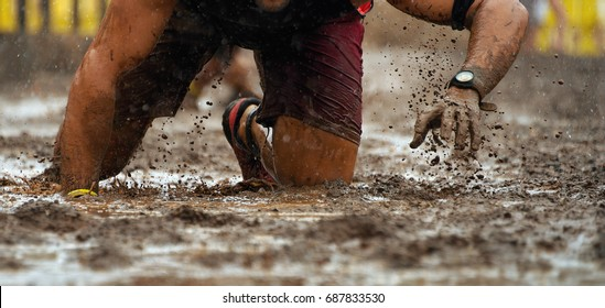 Mud race runners.Crawling,passing under a barbed wire obstacles during extreme obstacle race