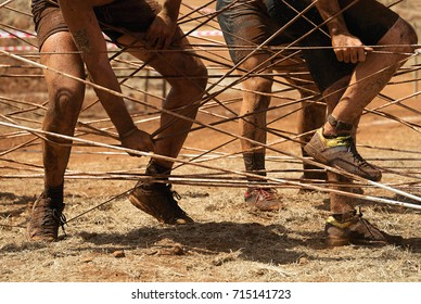 Mud race runners,racers overcome the obstacle from the ropes