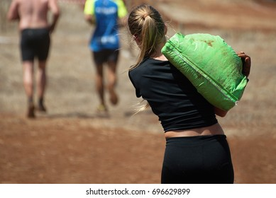 Mud race runners,young woman running with sandbag