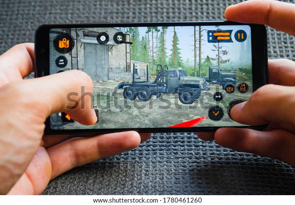 Mud runner. Game on android and ios mudrunner on a smartphone screen in male hands. Gameplay of the game mud runner on a smartphone on a black background. July 2020. Kiev, Ukraine