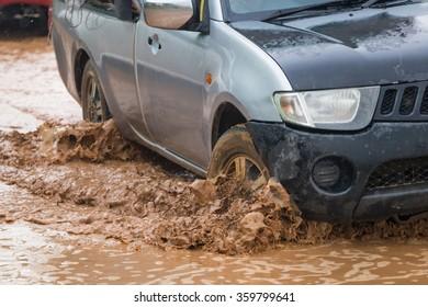 mud splash by a car as it goes through flood water