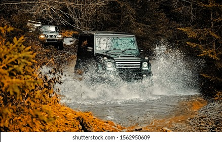 Mud and water splash in off-road racing. Off road sport truck between mountains landscape. Expedition offroader. Tracks on a muddy field. Road adventure. Adventure travel