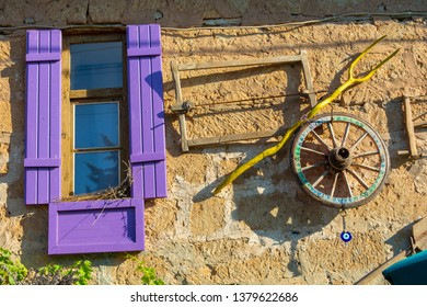 mudbrick house with purple shutters. Hanging agricultural equipment on wall