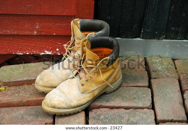 Mud-caked workboots on the brick walkway outside the black door to a bright red shed..