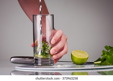 Muddling a lime wedges and minte leaves for making a Mojito cocktail