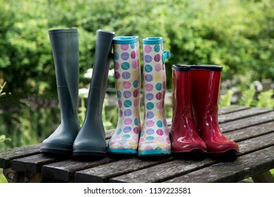 Muddy adults and kids wellington boots on an old picnic table