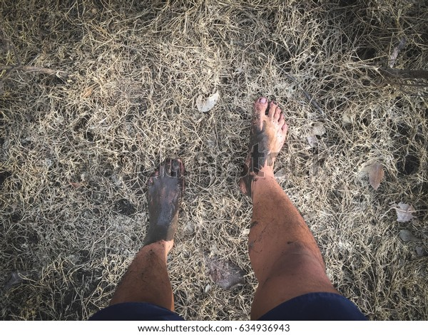muddy bare feet stand on dry field