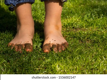 Muddy children feet. Young boy dirty feet on the grass. Dirty children foot on the grass. The little boy was playing in the mud, and his feet were completely dirty and muddy.