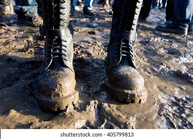 Muddy combat boots in the mud at the music festival