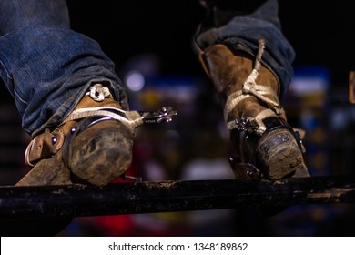 muddy cowboy boots with spurs on gate in Guatemalan rodeo