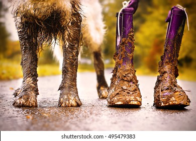 Muddy dog stands next to his owner with muddy boots