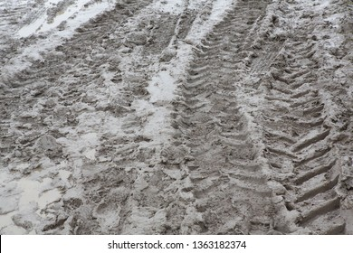 A muddy field with vehicle tracks and footprints in the mud.