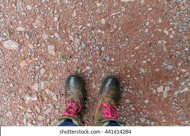 Muddy fishing/walking boots on a country stone and dirt path