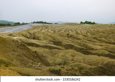 Muddy volcanoes. View of the muddy volcanoes with their unusual geology and cracked texture of the dry mud. Romania, out of focus.