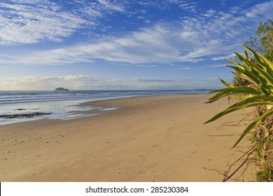 Mudjimba Beach Sunshine Coast, Queensland, Australia. Image shows Sandy beach with small waves, Mudjimba island and Point Cartwright on the horizon. Deep blue sky with clouds.