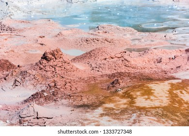 Mudpot in the geothermal area in Yelowstone National Park, Wyoming, USA. The area around the boiling mud is multicolored and cracked.