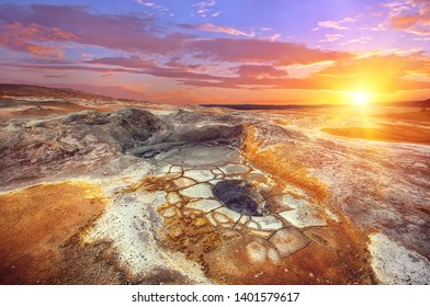 Mudpots in the geothermal area Hverir, Iceland. The area around the boiling mud is multicolored and cracked. Sunset time