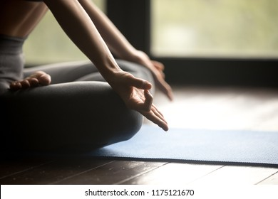 Mudra hands close up view. Sporty woman practicing yoga, doing Padmasana exercise, Half Lotus pose, working out wearing sportswear grey pants, indoor yoga studio. Healthy habits calm mind concept