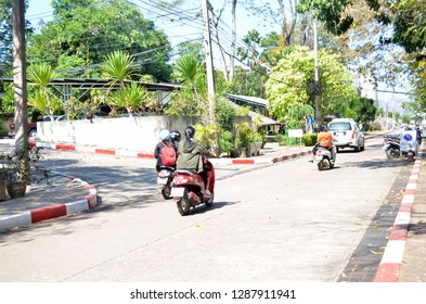 """""""Mueang Loei District, Loei province / Thailand - January 17th, 2019 : Loei Rajabhat University students riding motobikes on the roads within the area of the university, some riders wearing helmets"""