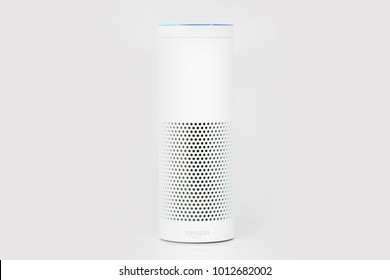 MUENSTER - JANUARY 27, 2018: White Amazon Echo Plus, Alexa Voice Service activated recognition system photographed on white studio backdrop, Packshot showing Amazon Logo