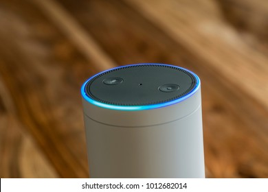 MUENSTER - JANUARY 27, 2018: White Amazon Echo Plus, Alexa Voice Service activated recognition system photographed on wooden table in living room, Packshot showing Amazon Logo