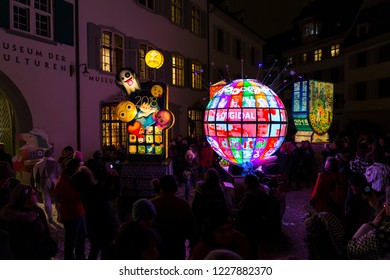 Muensterplatz, Basel, Switzerland - February 20th, 2018. Basel carnival. Three beautiful illuminated carnival lanterns with a watching crowd of people