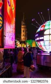 Muensterplatz, Basel, Switzerland - February 20th, 2018. Basel carnival. View between illuminated lanterns on the Basel minster with a crowd of people in front