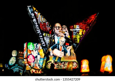Muenzgasse, Basel, Switzerland - March 11th, 2019. Three colorful tall illuminated main lanterns during the carnival morgestraich parade.