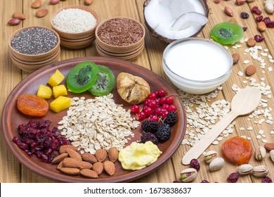 Muesli balanced protein breakfast. Fruits, berries  seeds, nuts, coconut. Healthy Diet vegetarian food. Top view Wooden background.