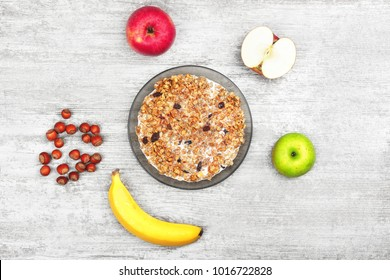 Muesli with banana, apple and nuts. Bowl of porridge with fruits and milk on the wooden gray background. Wholesome breakfast. Healthy food. Top view. Vegetarian lifestyle. Slimming and diet.