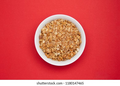 Muesli with banana in a white bowl on red background