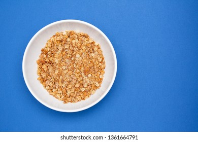 Muesli with banana in a white bowl on blue background