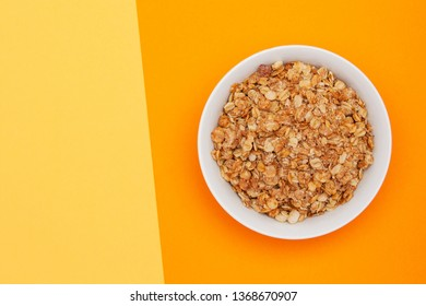 Muesli with banana in a white bowl on yellow and orange background with copyspace