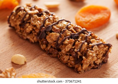 Muesli bar with chocolate and dried apricots on wooden board close-up
