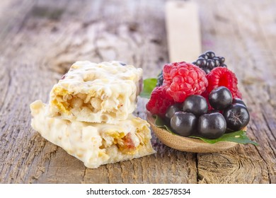muesli bars with fresh berries in spoon on wooden background