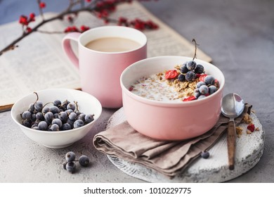 muesli with berries and a cup of coffee with milk