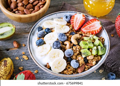muesli bowl with sliced banana, blueberry, kiwi and strawberry on wooden table, closeup view. Healthy eating, healthy breakfast dieting concept