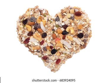Muesli - cereal flakes with seeds, mixed fruit and nuts - in a heart shape, isolated on a white background