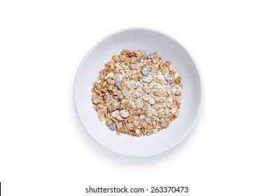 Muesli cereal with nuts and raisins in a white bowl shot from above isolated on white with path