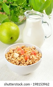 Muesli with dried fruit, jug of milk and apple